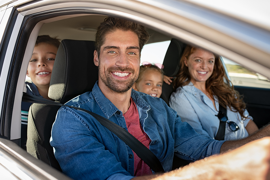 Personal Insurance - Happy Family Posing and Smiling in their Car Before Leaving to go on a Vacation